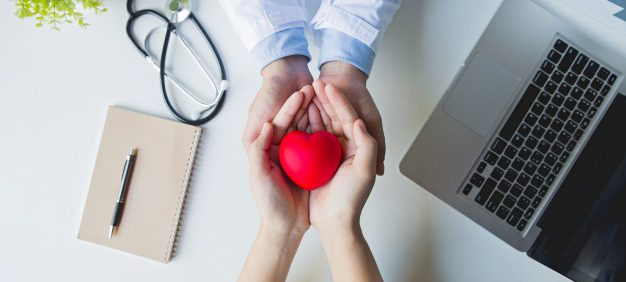 top-view-doctor-patient-hands-holding-red-heart-white-table_38391-541
